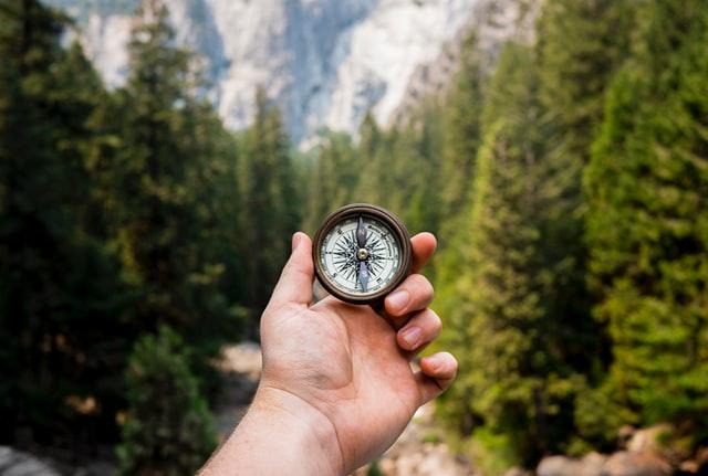 image d'une main tenant un GPS de randonnée version boussole en pleine nature
